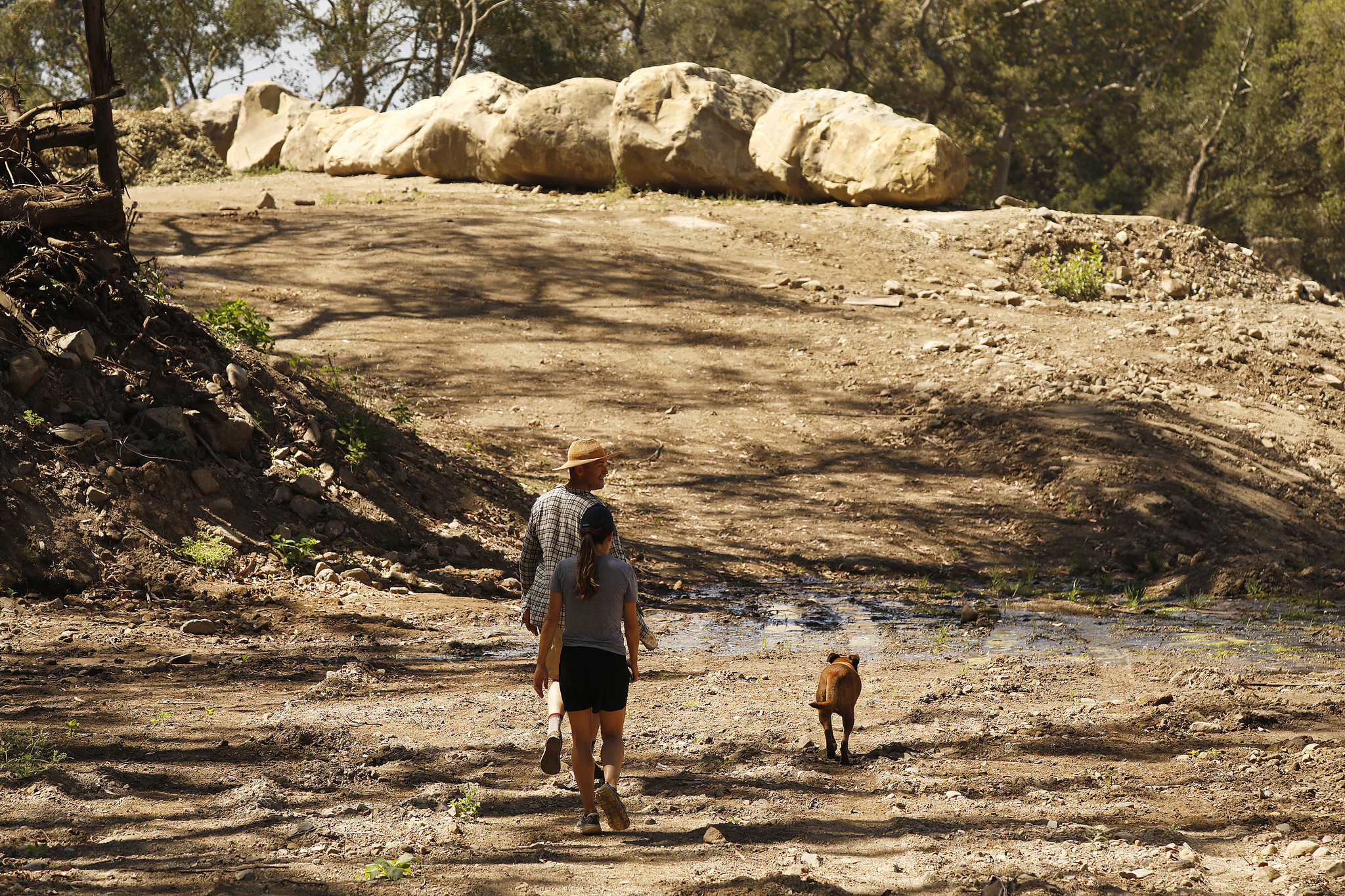 Hikers walk as debris is cleared at the San Ysidro Debris Basin in the hills above Montecito June 12, 2018.