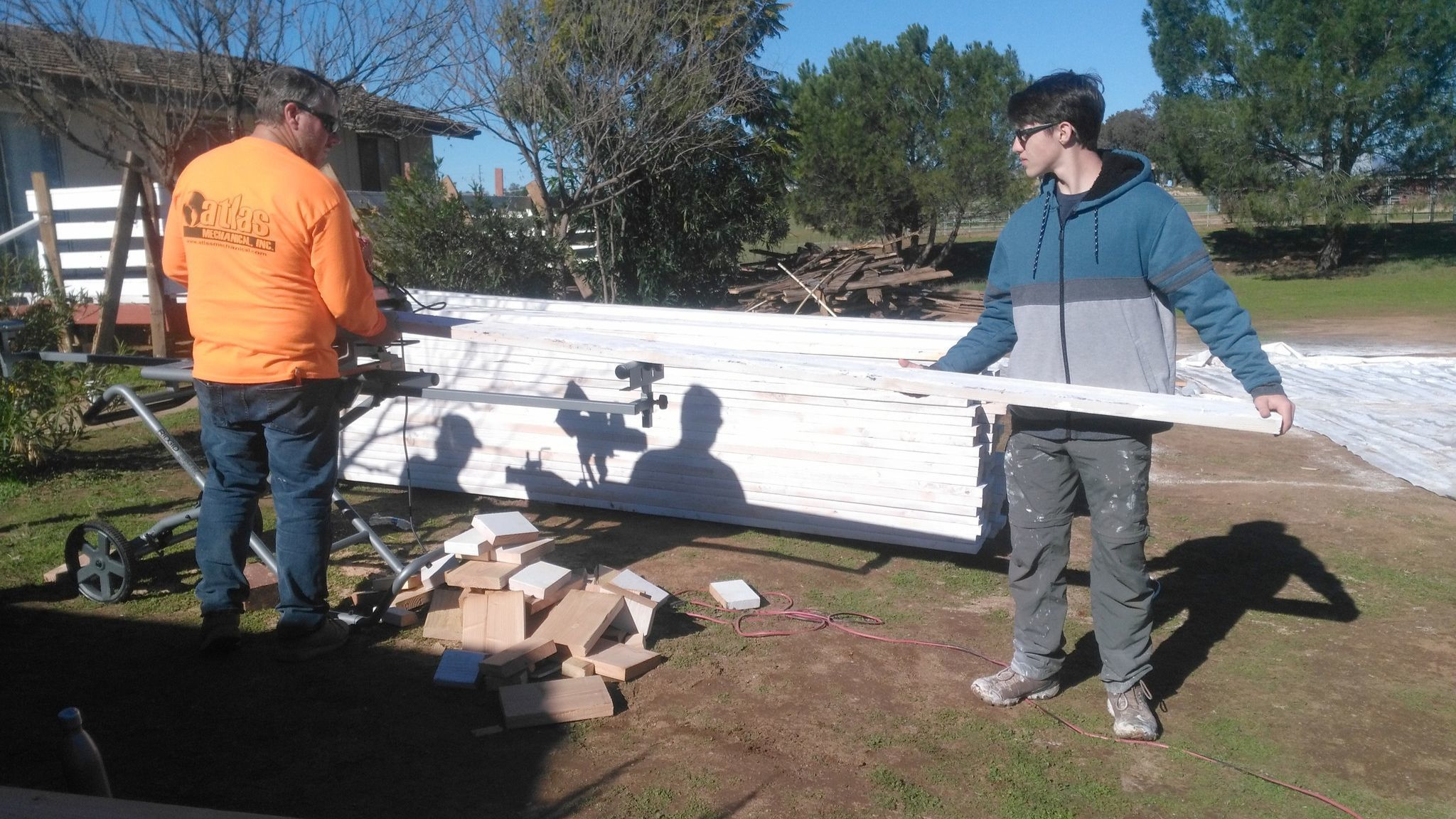 James White, right, works with his father, Robert White, on cutting boards for a new deck at Michael's House.