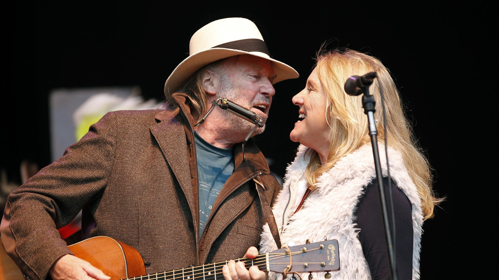 FILE - In this Oct. 24, 2010 file photo, Neil Young, left, and his wife Pegi Young perform during th