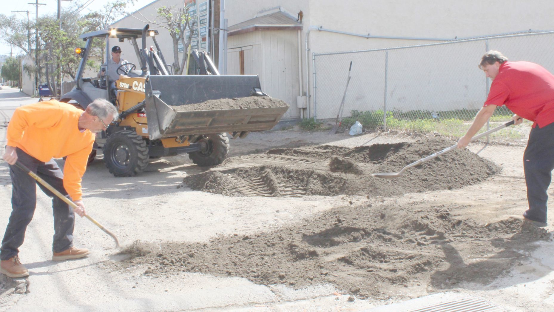 Jim Piva works the bobcat while John Thompson and Mike Morgart shovel decomposed granite road mix into deep potholes in the alley behind 7-Eleven and Jack in the Box in April.