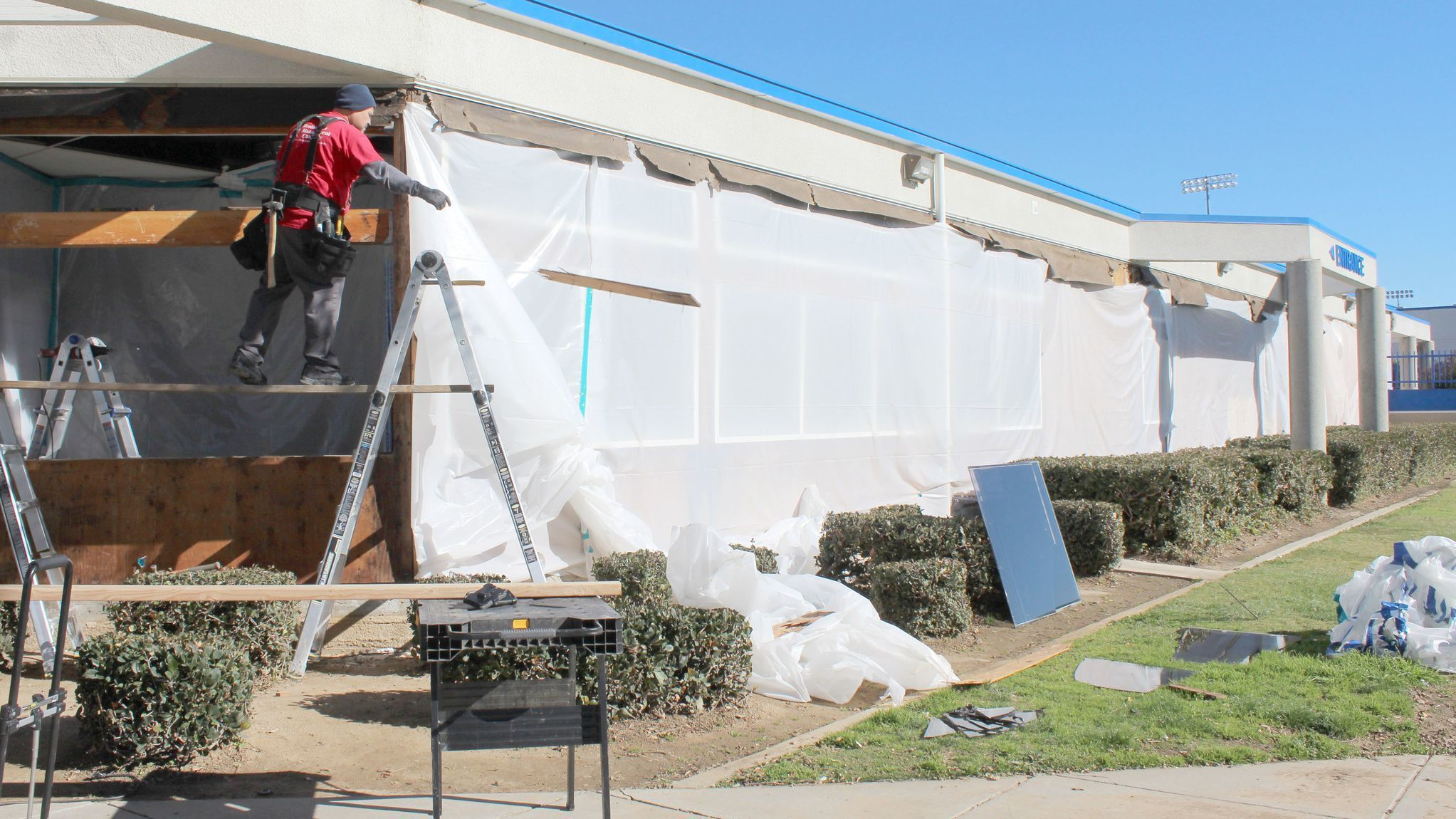 Bakersfield resident Eduardo Vegas, a Restoration Management Co. employee, replaces Ramona High School Administration Building windows with new energy-efficient windows.