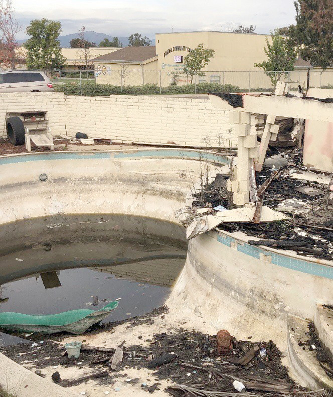 View of filthy pool with Ramona Community Campus across the street.