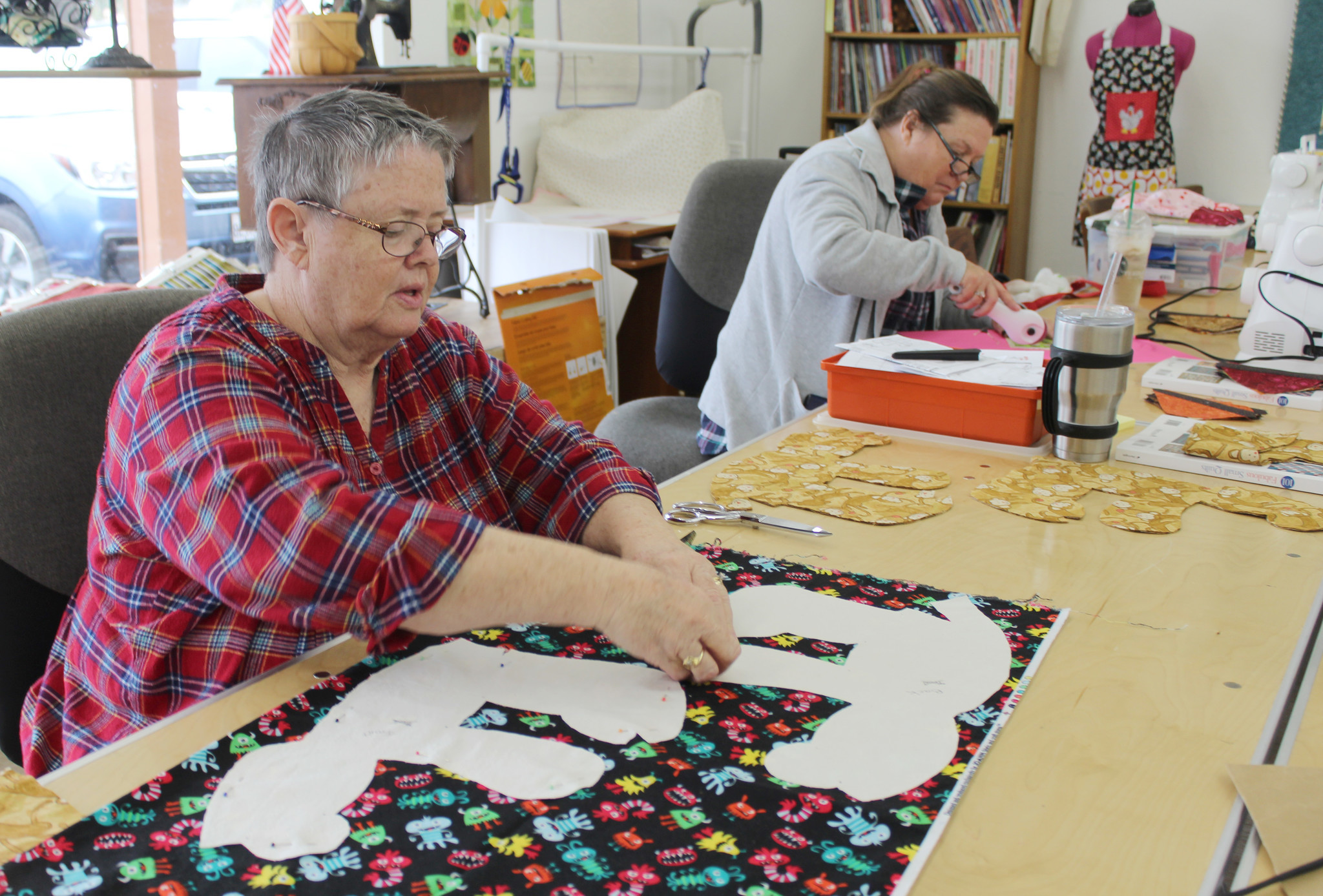 Jan Moran cuts a bear pattern. In the  background is Beth Edmonds.