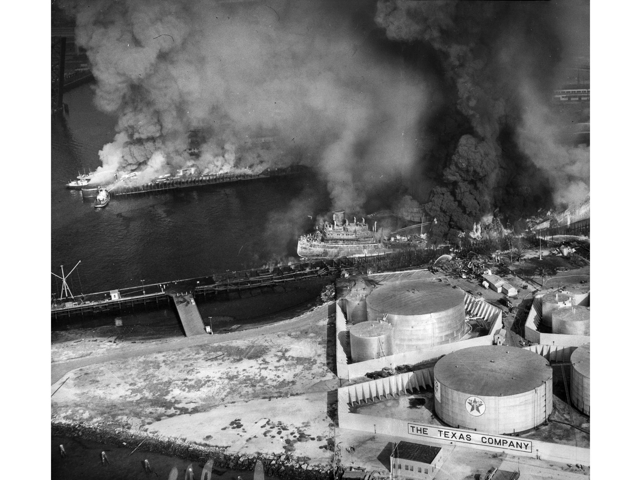 June 22, 1947: The Markay, along dock in channel, burns close to Texas Co. oil storage taks in foreg