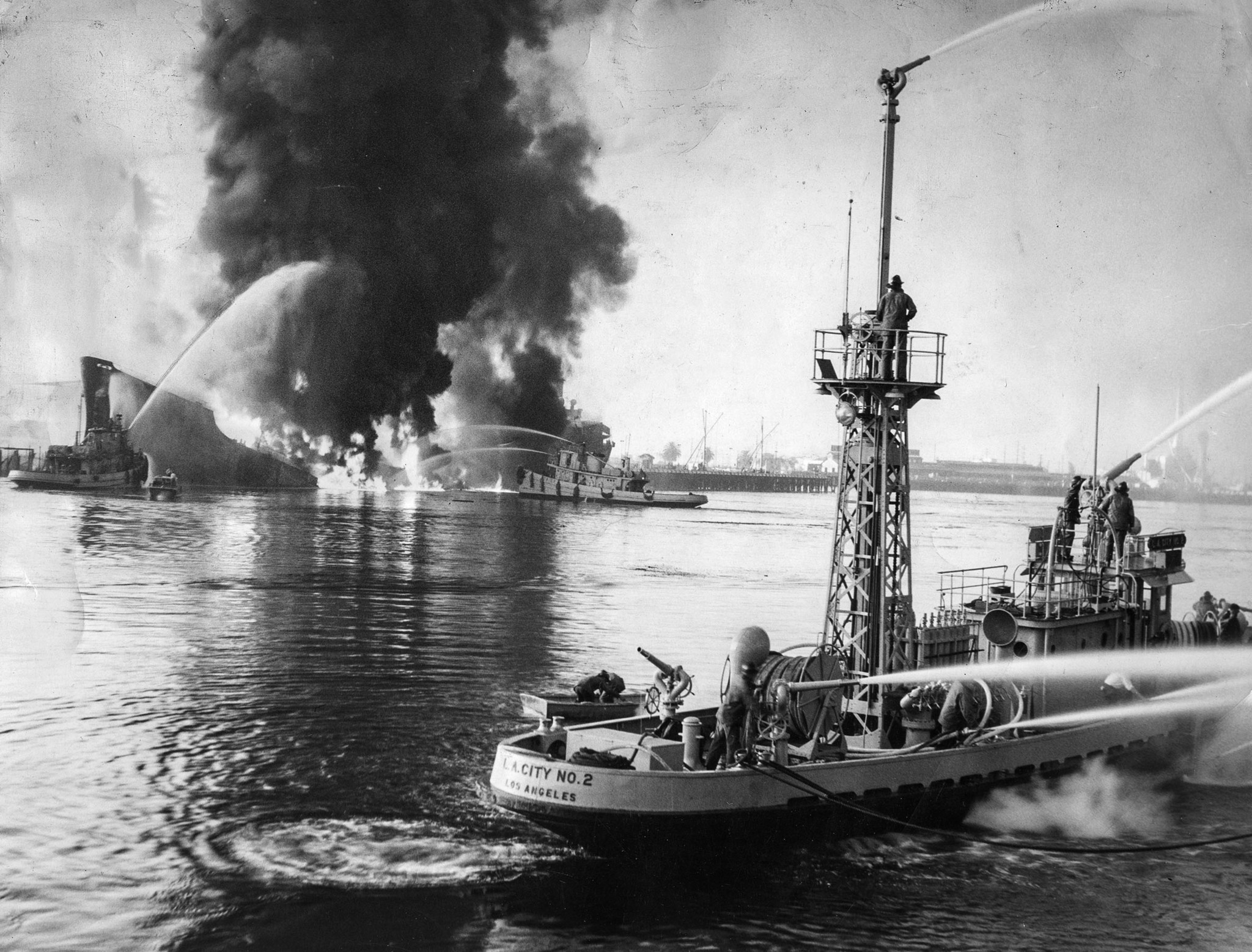 June 22, 1947: Fireboats play streams of water on the burning tanker S.S. Markay, background, after