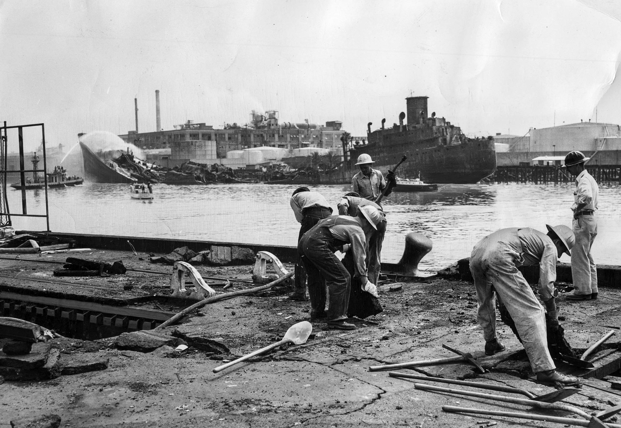 June 23, 1947: The day after an explosion destroyed the tanker S.S. Markay, background, workers tear