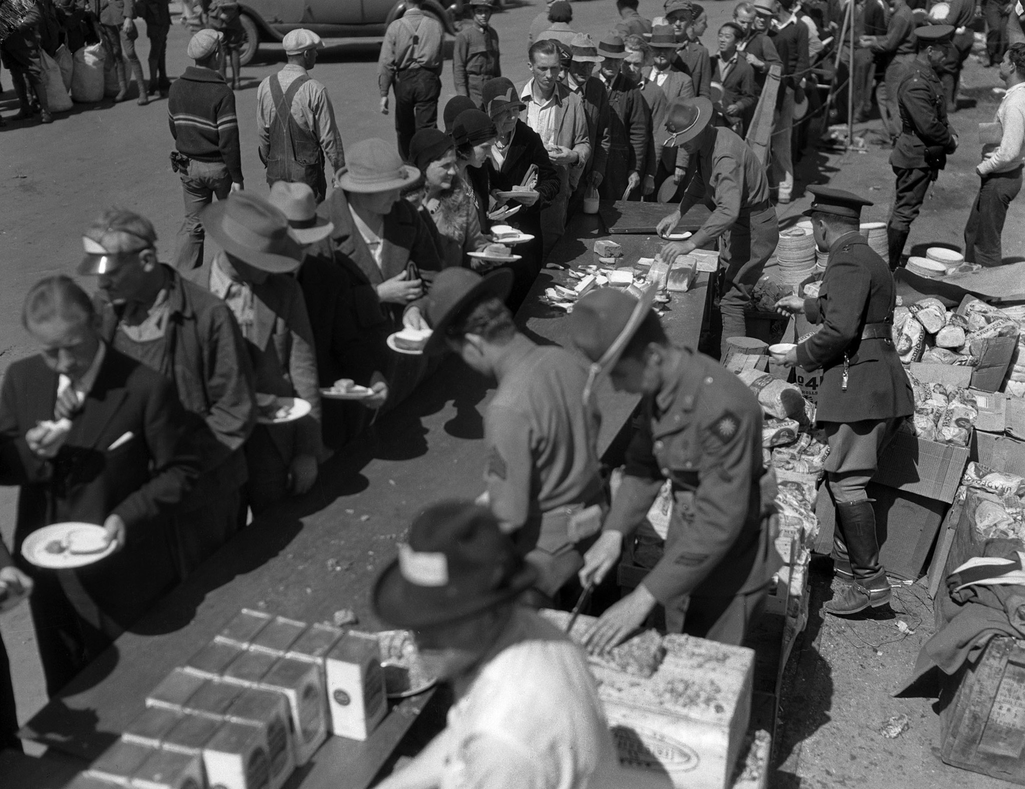 People in line holding plates of food after the March 10, 1933, Long Beach earthquake. Appears to be