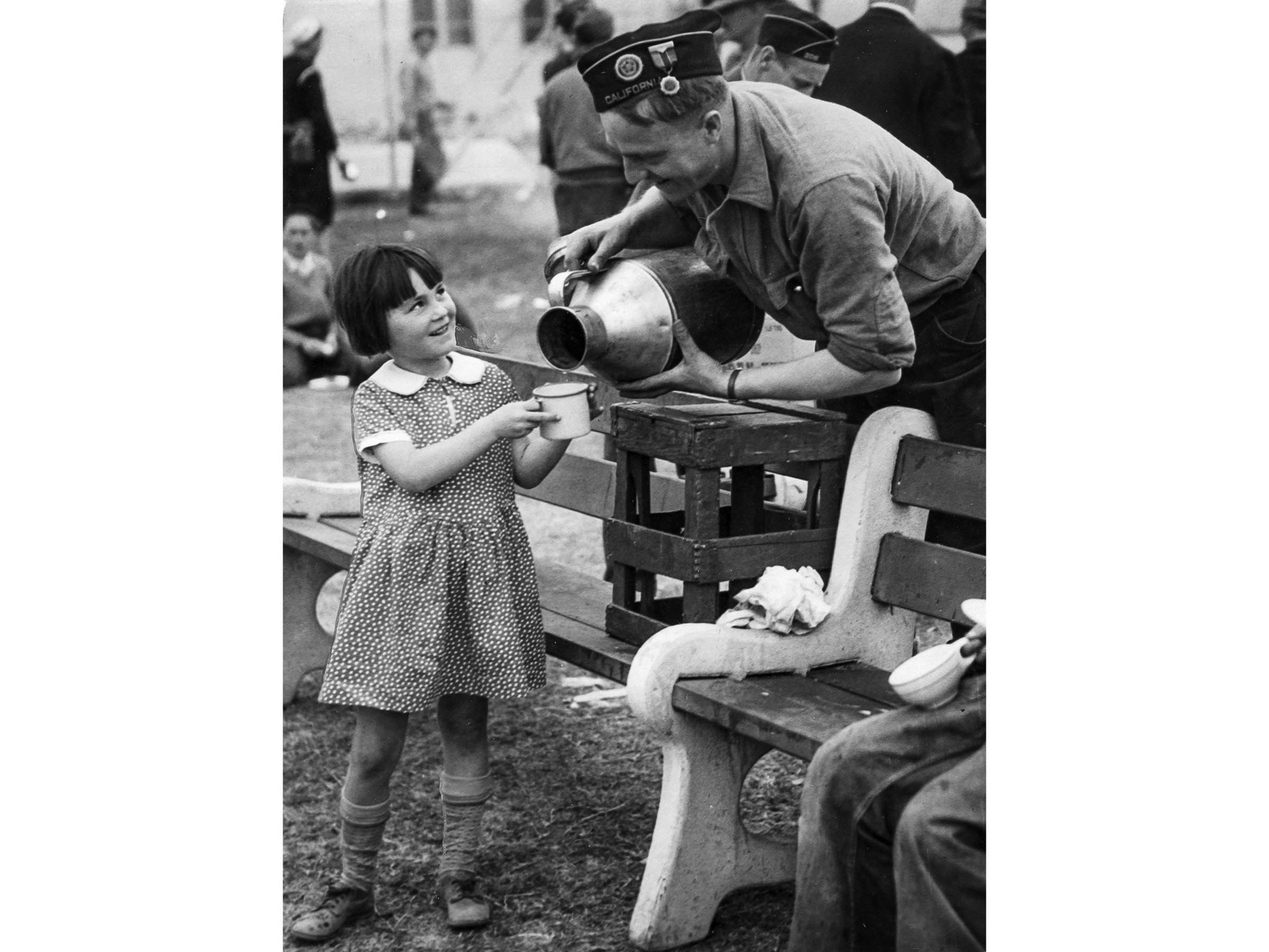 March 13, 1933: Barbara Jean McMannis get a cup of milk from American Legionaire volunteer at City H