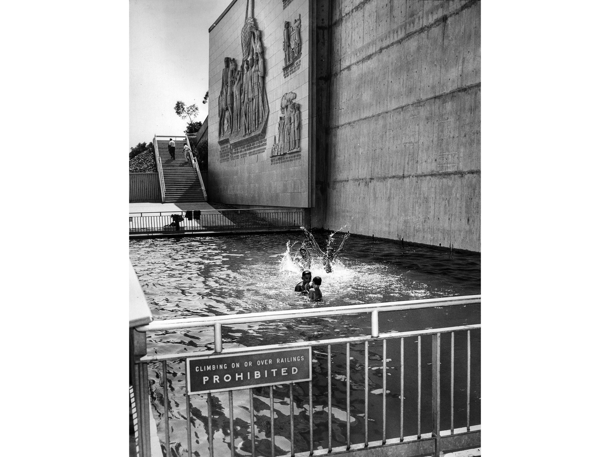 July 9, 1957: Four boys ignore sign prohibiting entering pool at base of Fr. Moore Memorial, and mer