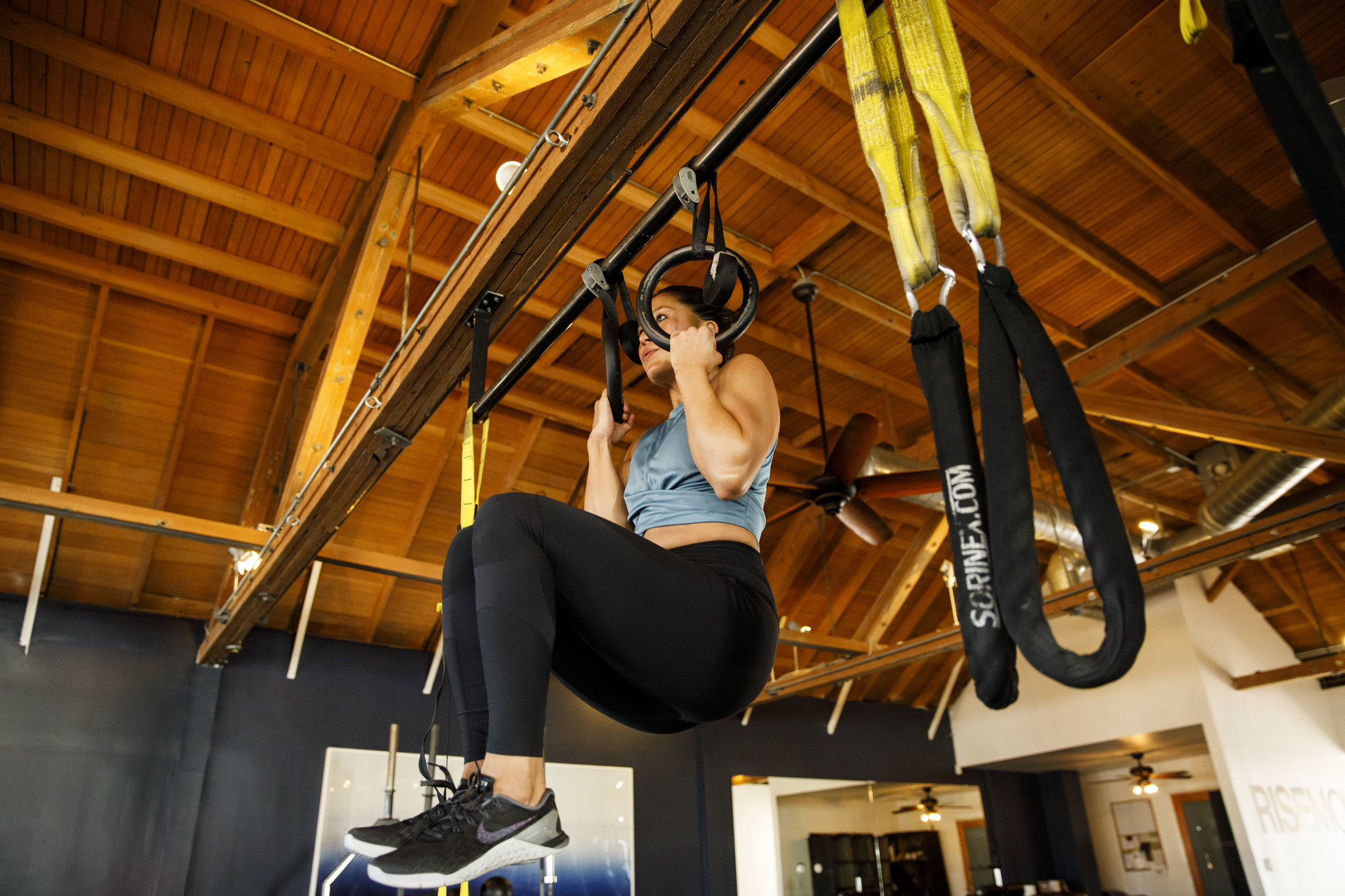 Trainer Alyssa Shoji demonstrates exercises on the rings at the gym Rise Movement on Saturday, Febru
