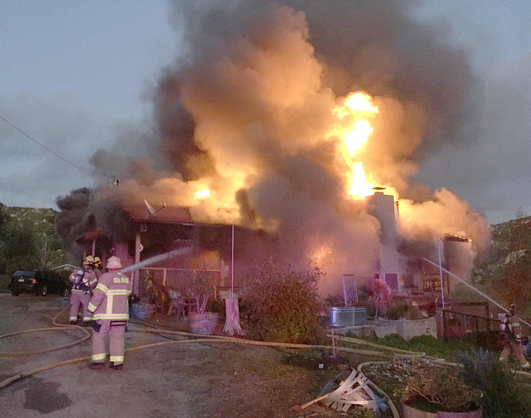 As flames shoot in the air, firefighters contain the blaze to the home.