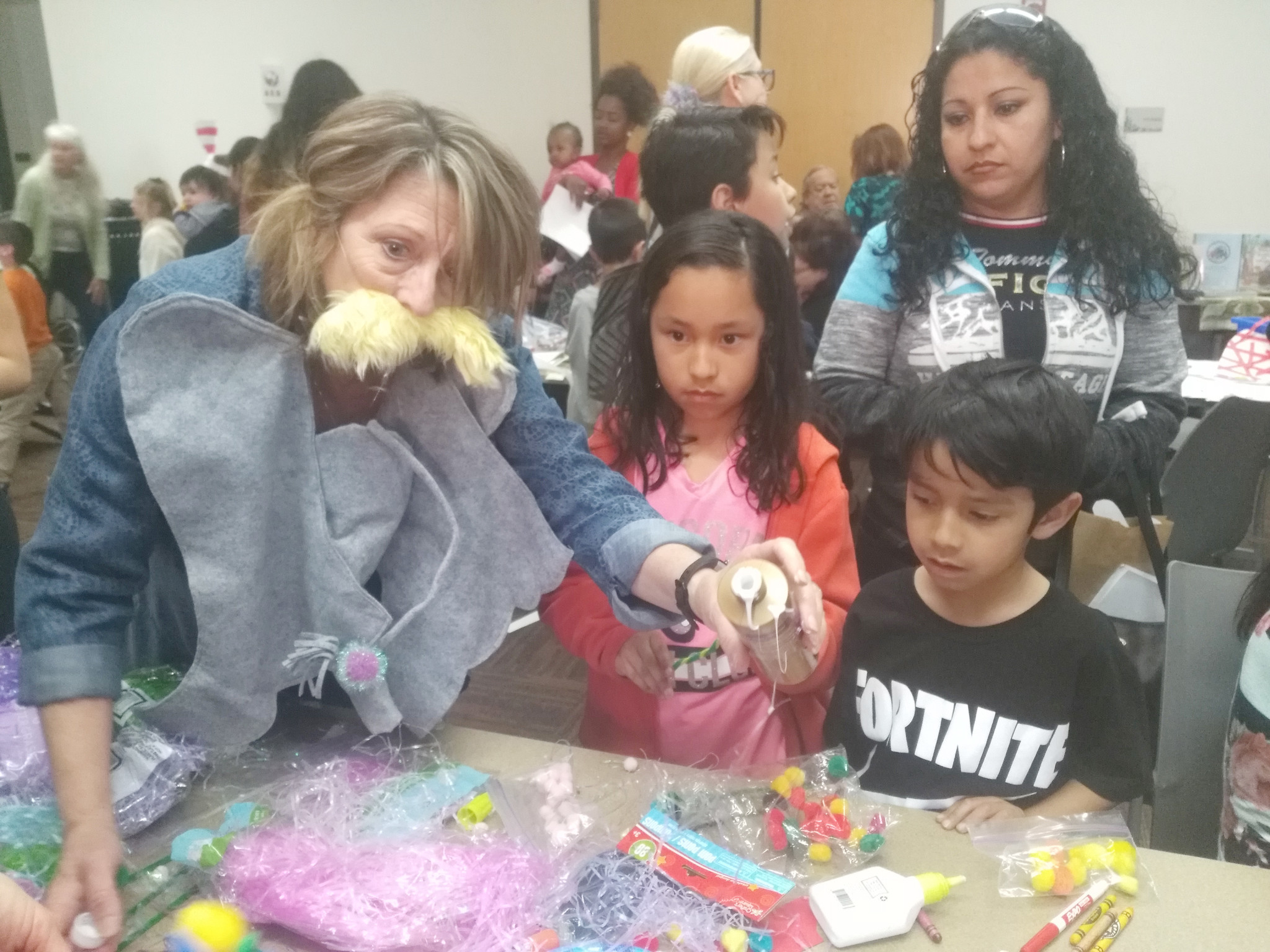 Iota Rho member Donna Braye-Romero, left, shows the Mendoza family how to assemble their crafts. In front are Jacqueline and Daniel, and behind are Marco and Eva.