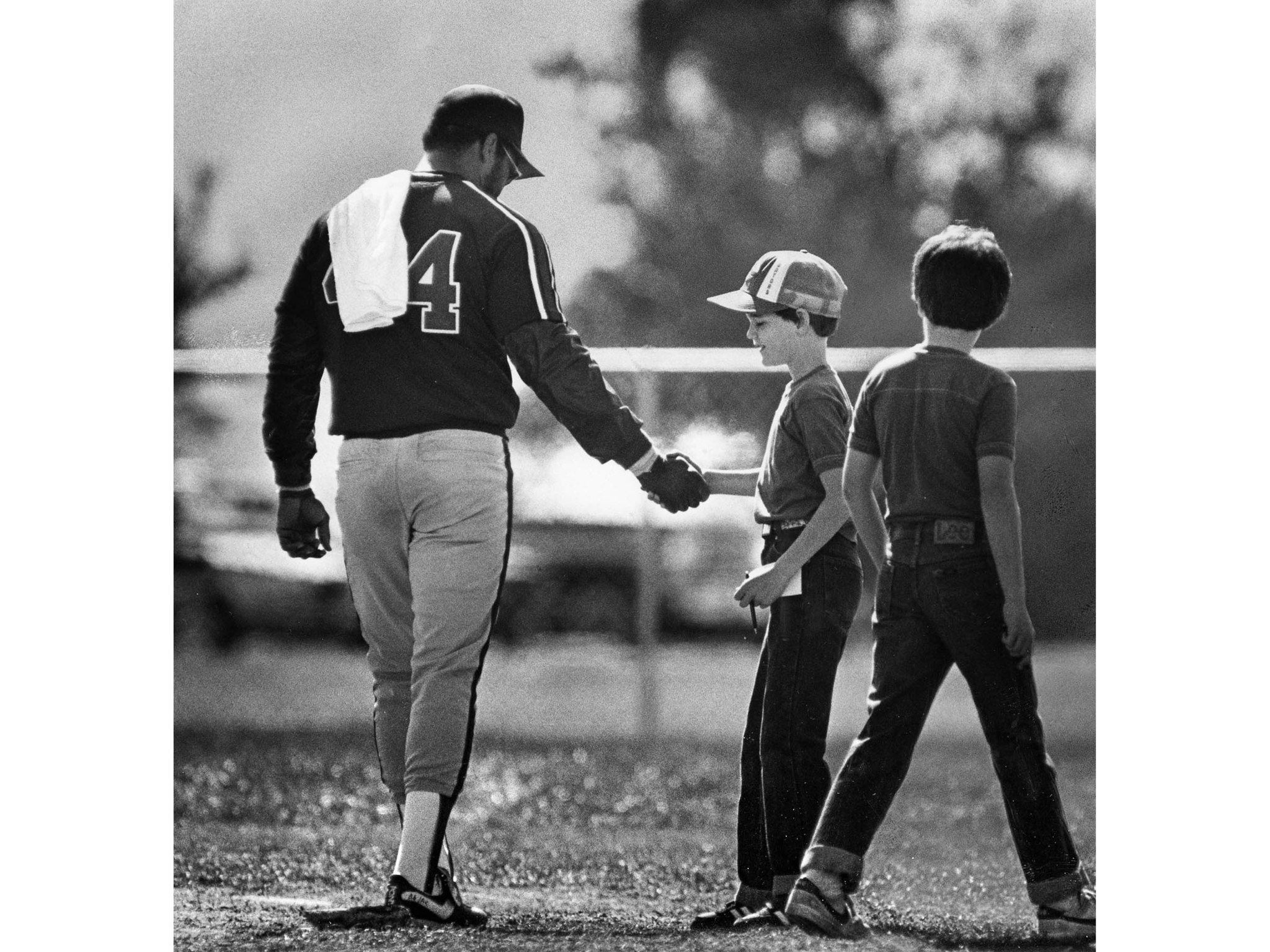 March 1983: Angels slugger Reggie Jackson shakes hand of young admirer before leaving practice field