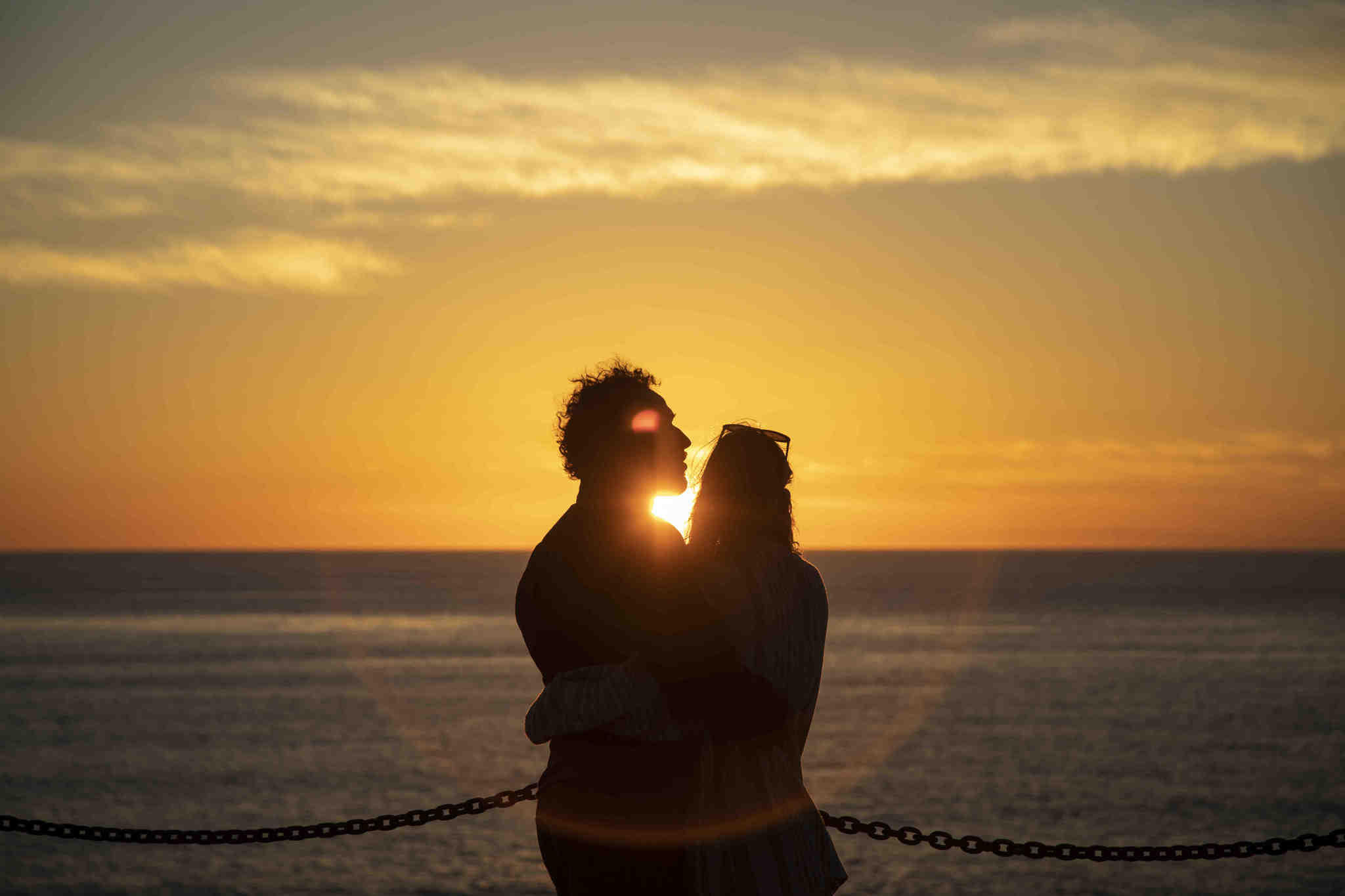 SAN DIEGO, CA - February 27, 2019 - A couple watching the sunset at Sunset Cliffs Natural Park in Sa