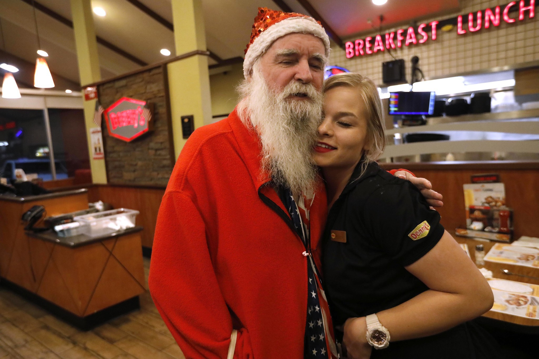 James Zyla gets a hug from waitress Kaylene Purcell, 17, at a Denny's restaurant in Kingman. Purcell helped Zyla get a gig at the Ramada Hotel where he played his keyboard for fr