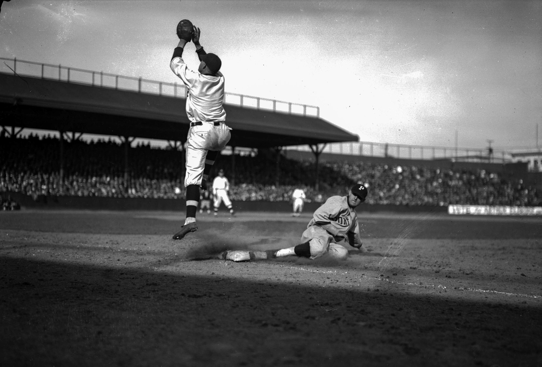 April 7, 1925: Los Angeles Angels' first baseman Ray Grimes leaps high during a pickoff attempt of P