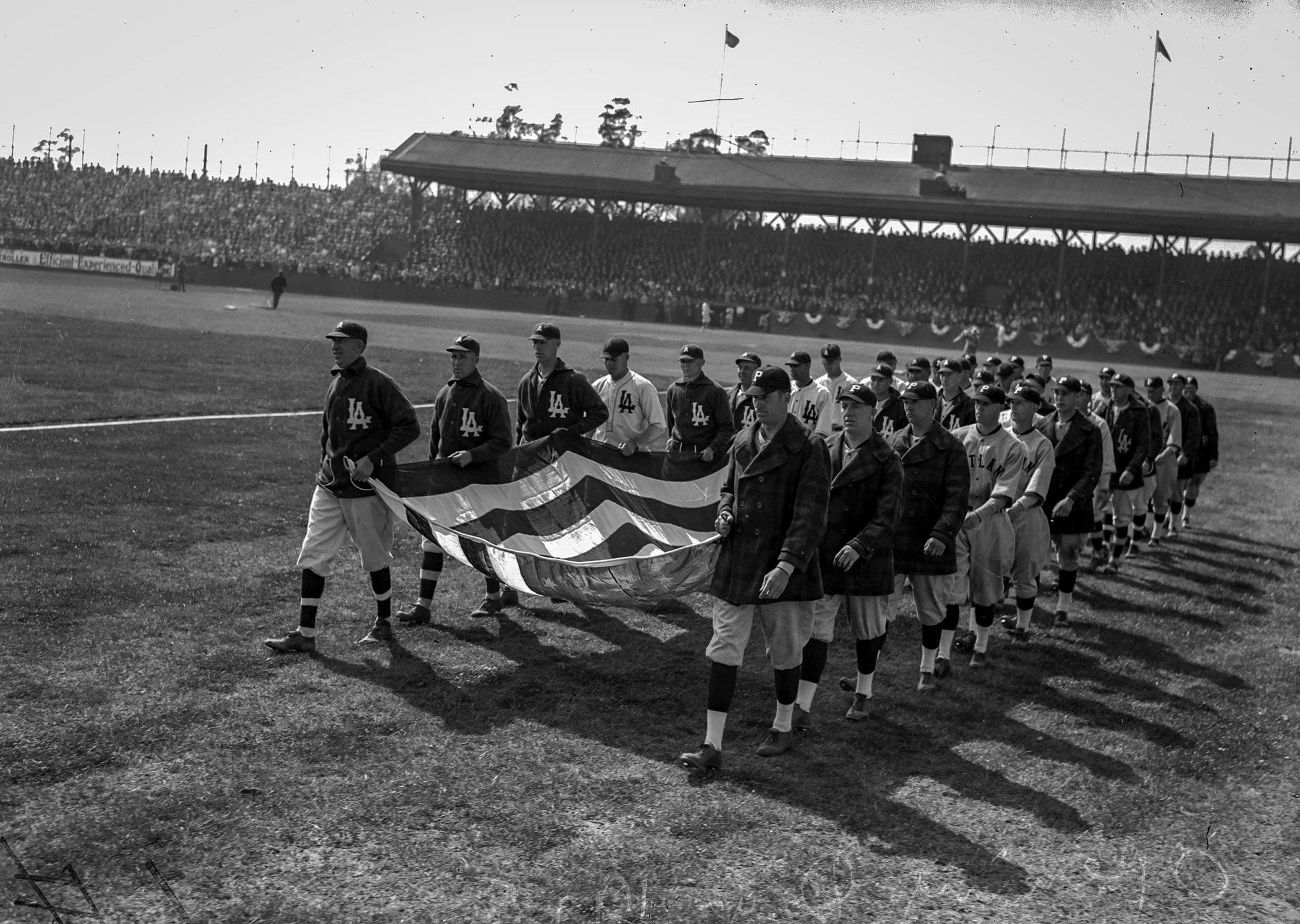 April 7, 1925: Members of the Los Angeles Angels and Portland Beavers carry Old Glory out onto field