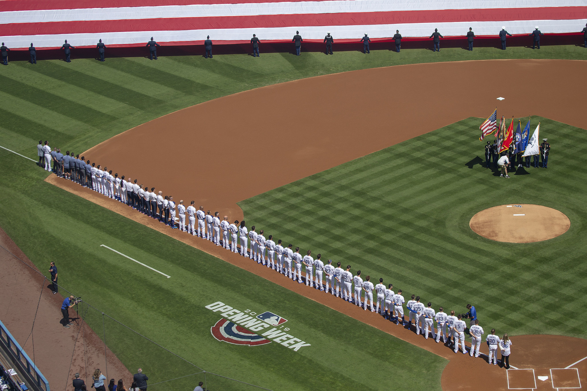LOS ANGELES, CALIF. -- THURSDAY, MARCH 28, 2019: The Dodgers line the field as a giant American flag