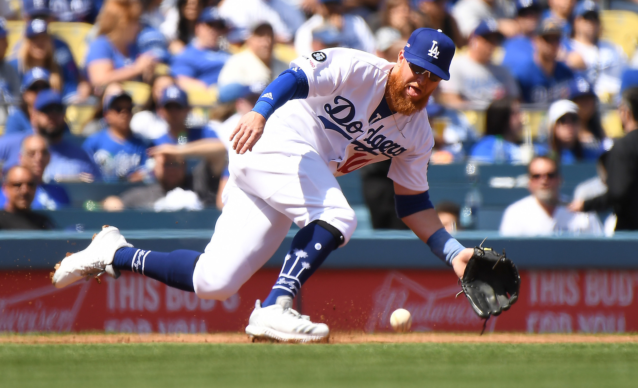 LOS ANGELES, CALIFORNIA MARCH 25, 2019-Dodgers third baseman Justin Turner leans to catch a ground bal