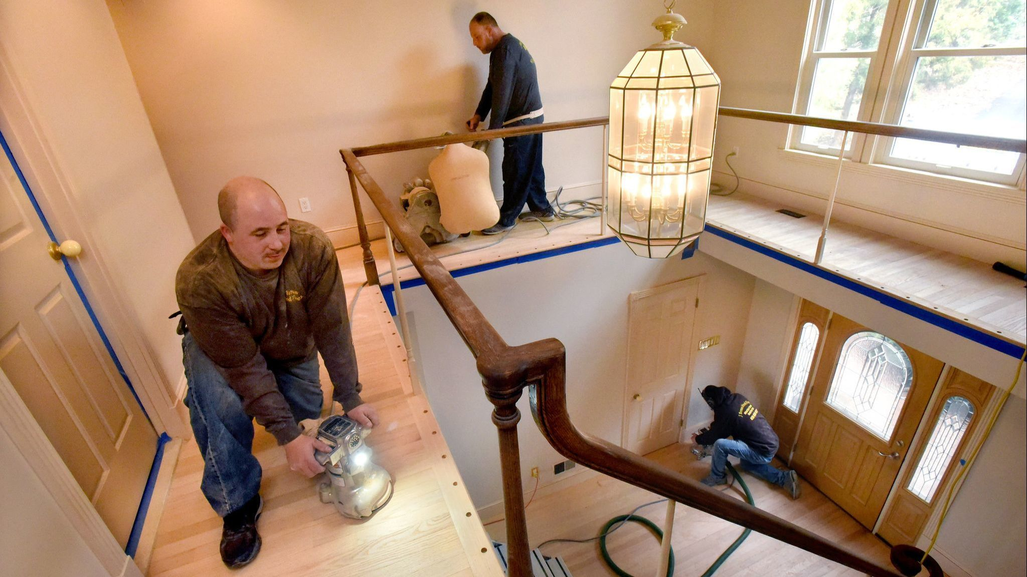 Jason Brown, in front, and members of his crew sand the red oak floors in a Severna Park home before