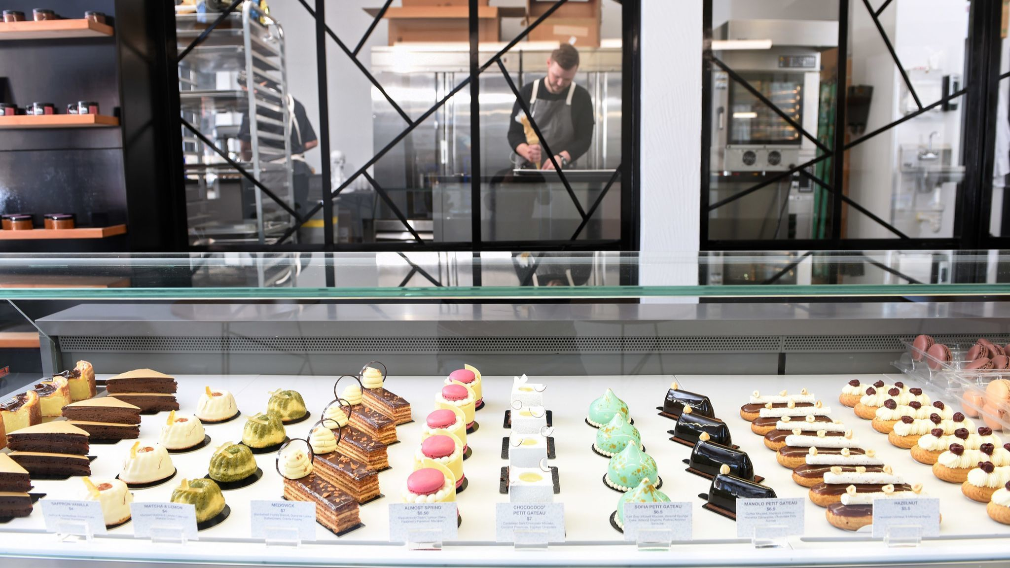 Dane Thibodeaux fills macarons in the kitchen of his pastry studio, located at 200