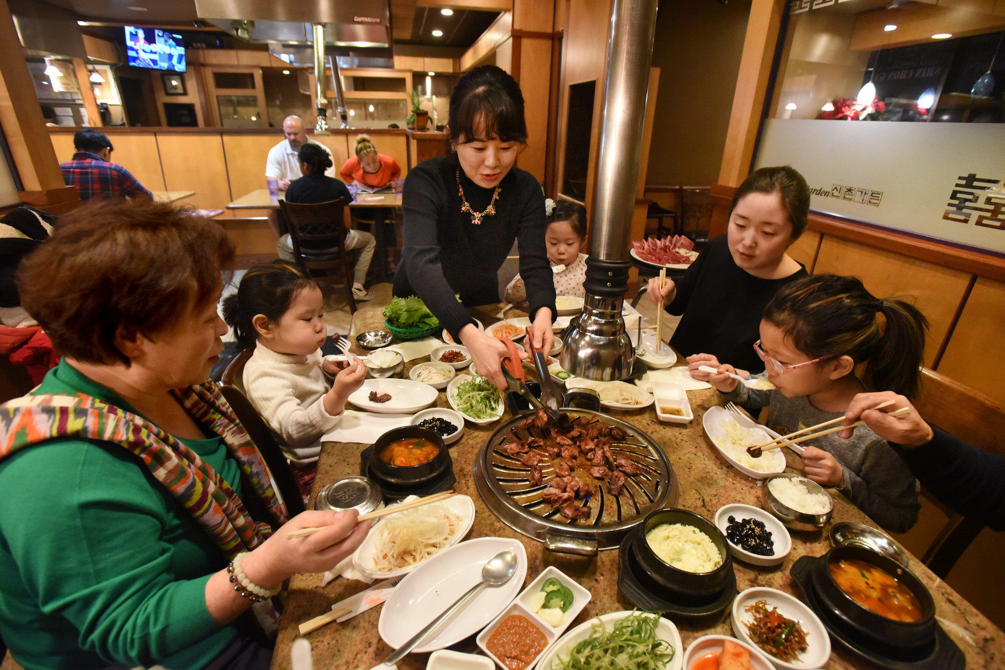 Miha Lee, of Shin Chon, cuts beef on the table grill for the barbecue feast enjoyed by the Ahn famil