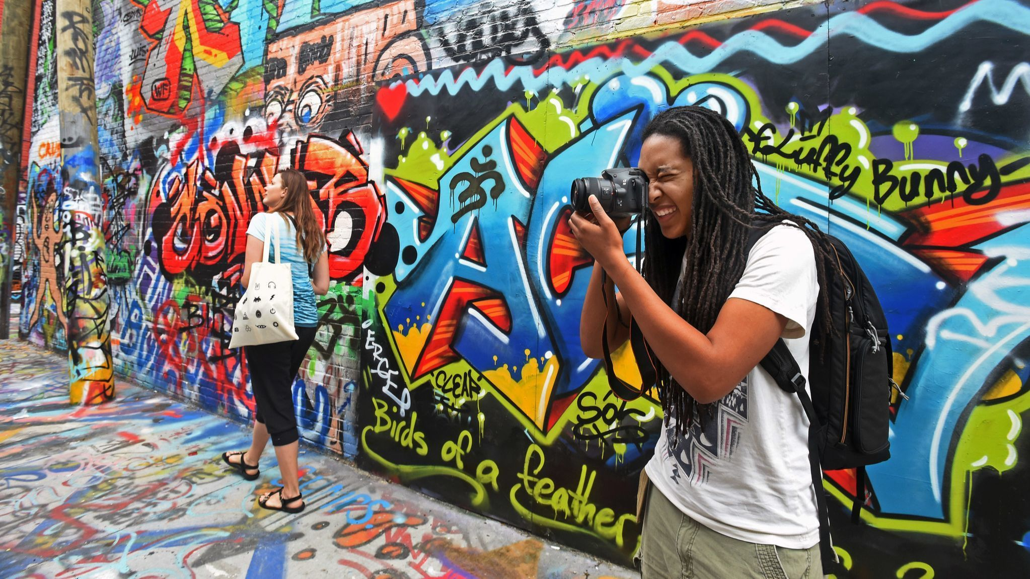 """Baltimore, Md.--4/30/17-- Noel Webster, of Baltimore, takes pictures at """"graffiti alley"""" while on Ba"""