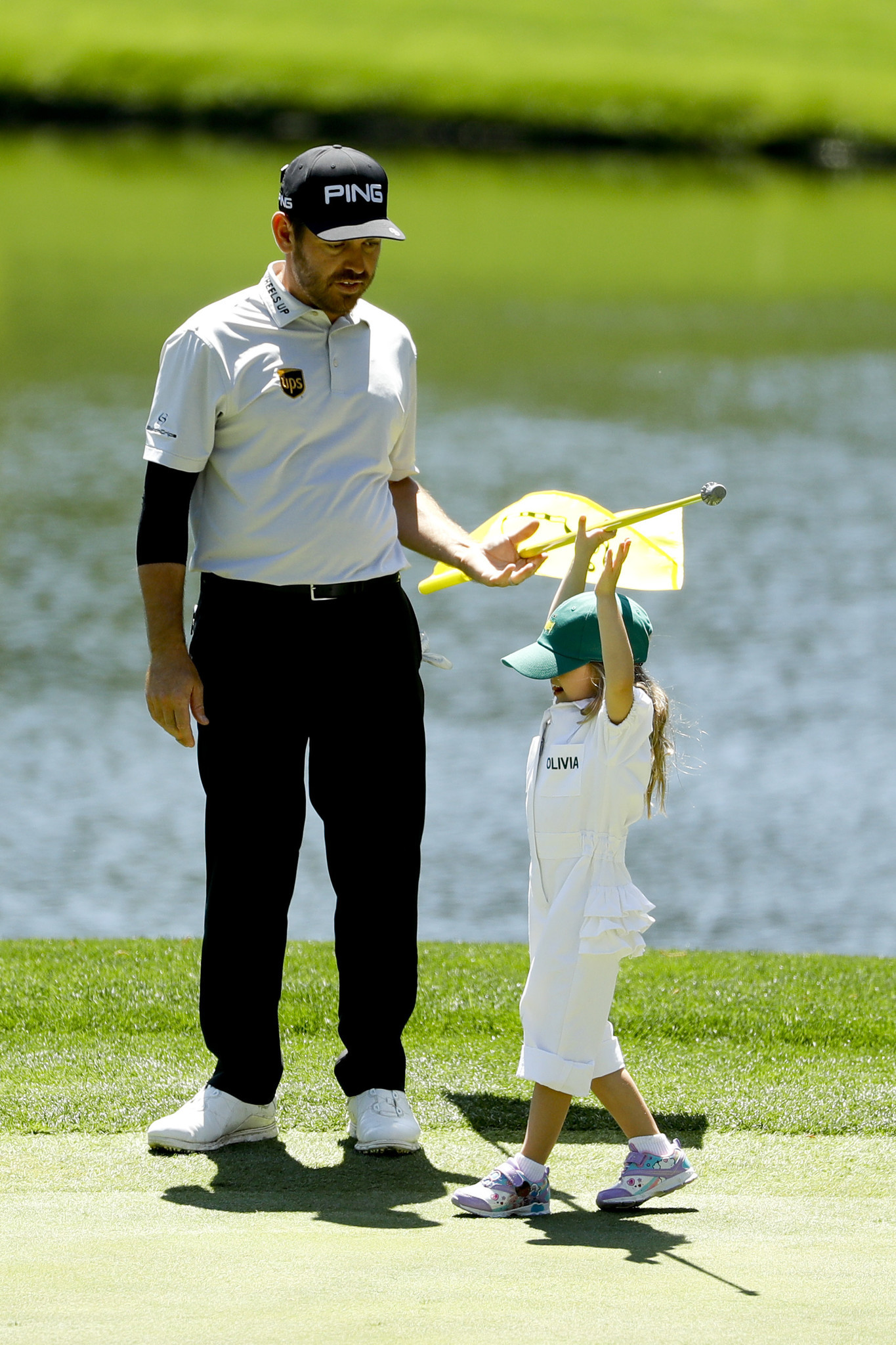 Louis Oosthuizen, of South Africa, helps his daughter Olivia pull the flag on the third hole during