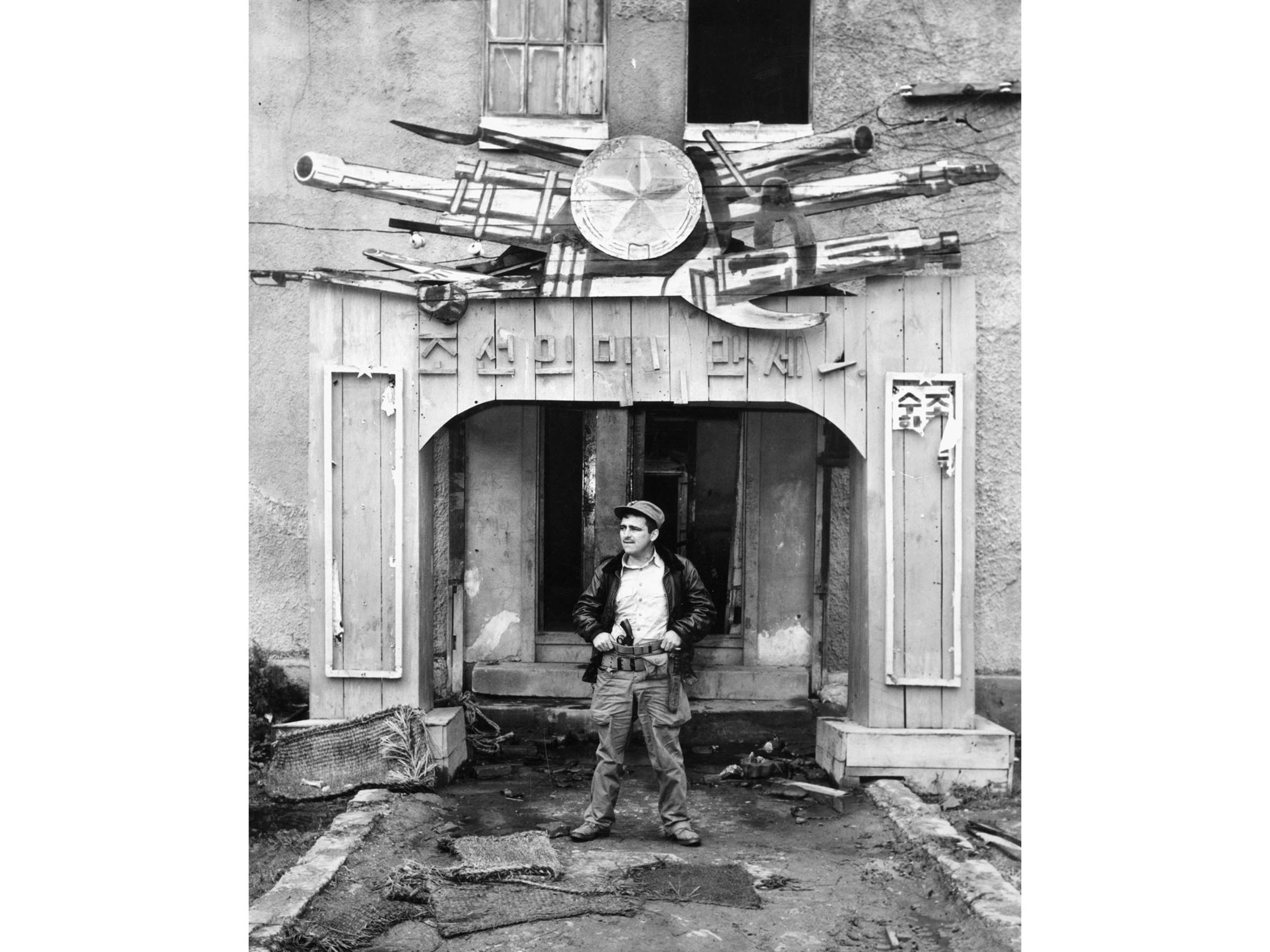 1950: Self portrait of Marine Sgt. Bill Murphy in front of former Communist Headquarters in Wonsan,