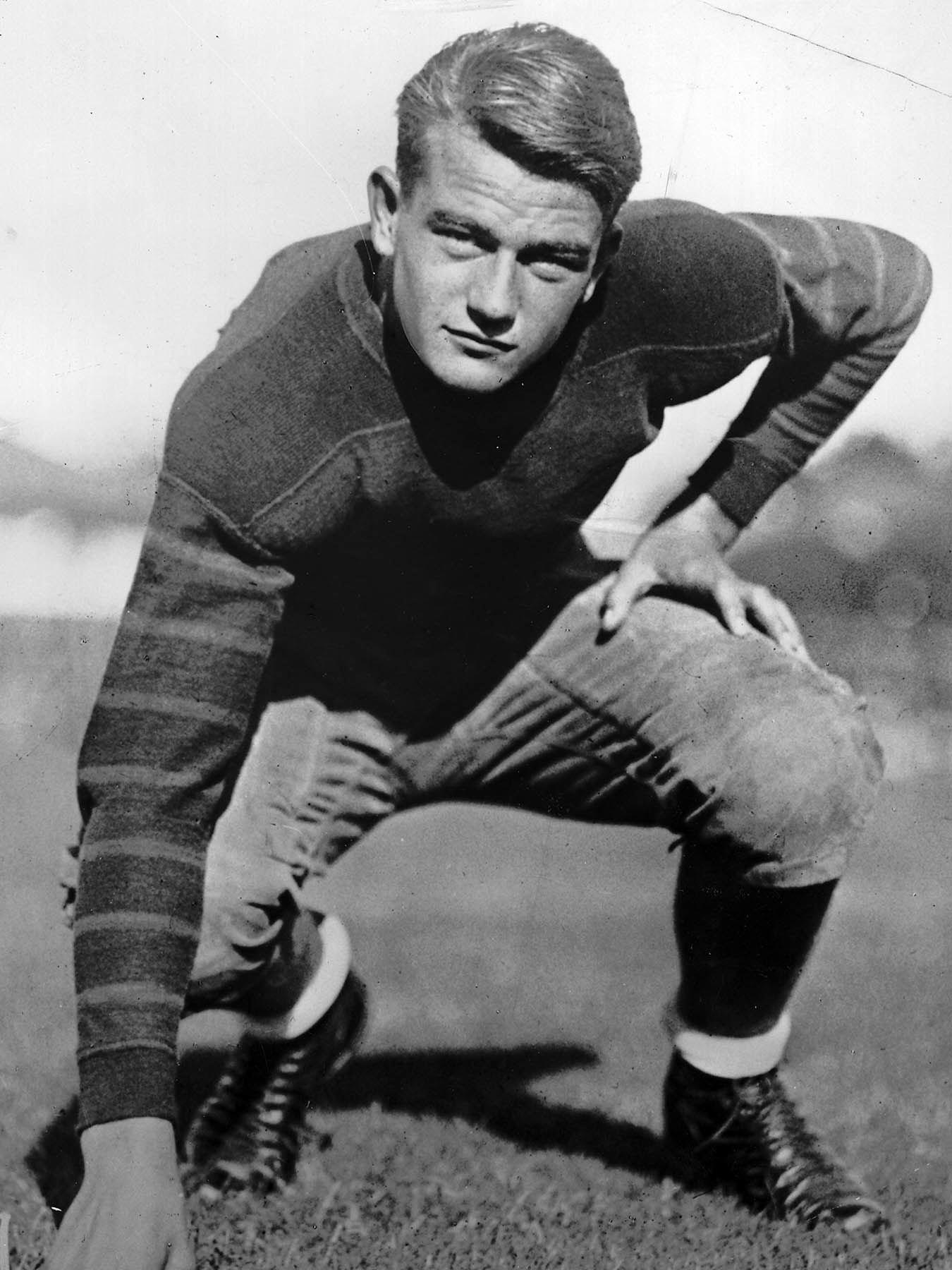John Wayne appears in battle garb he wore as a member of the undefeated Trojan frosh. He played unde