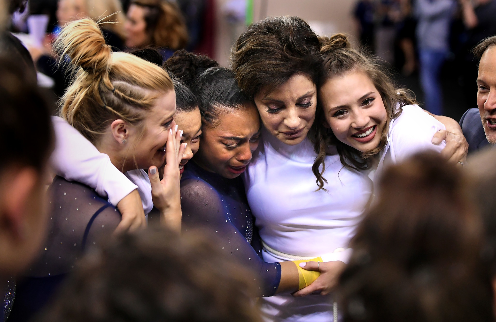 Coach Valorie Kondos Field, second from right, hugs her gymnasts from left, Gracie Kramer, Anna Glenn, Margzetta frazier and team manager Lila Waller.