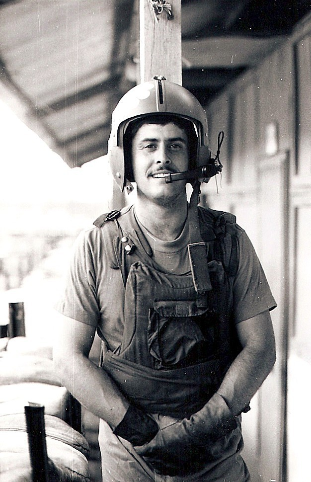 This photo shows Junkins at the top-secret Studies and Observations Group at Phu Bai, South Vietnam. He is wearing a helicopter crewmember helmet and protective vest.