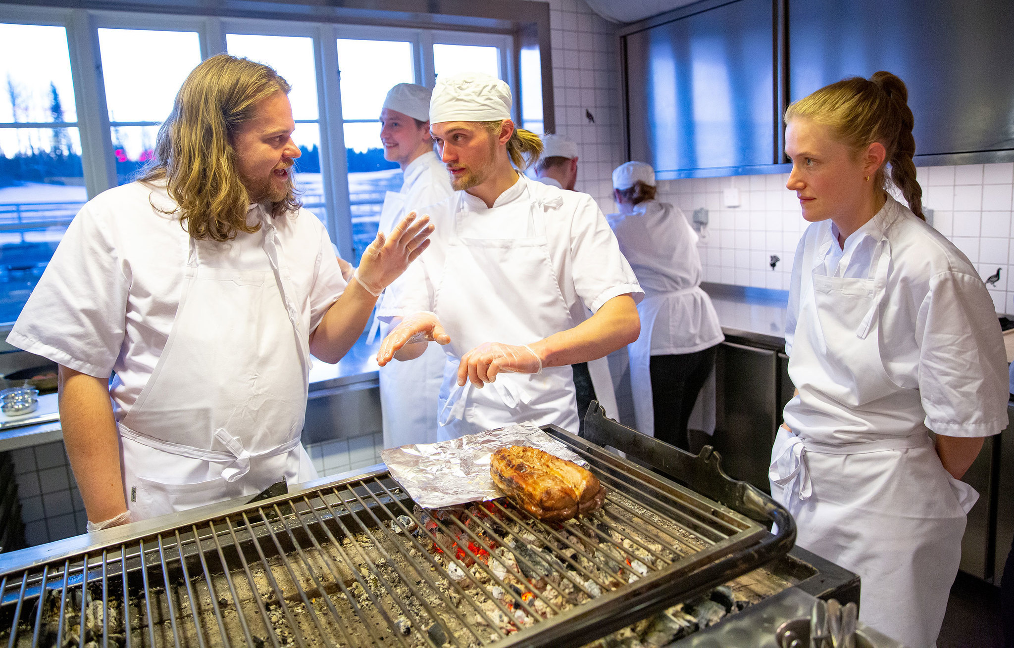 Head chef Magnus Nilsson talks with his staff while preparing a saddle of veal over an open fire at Faviken.
