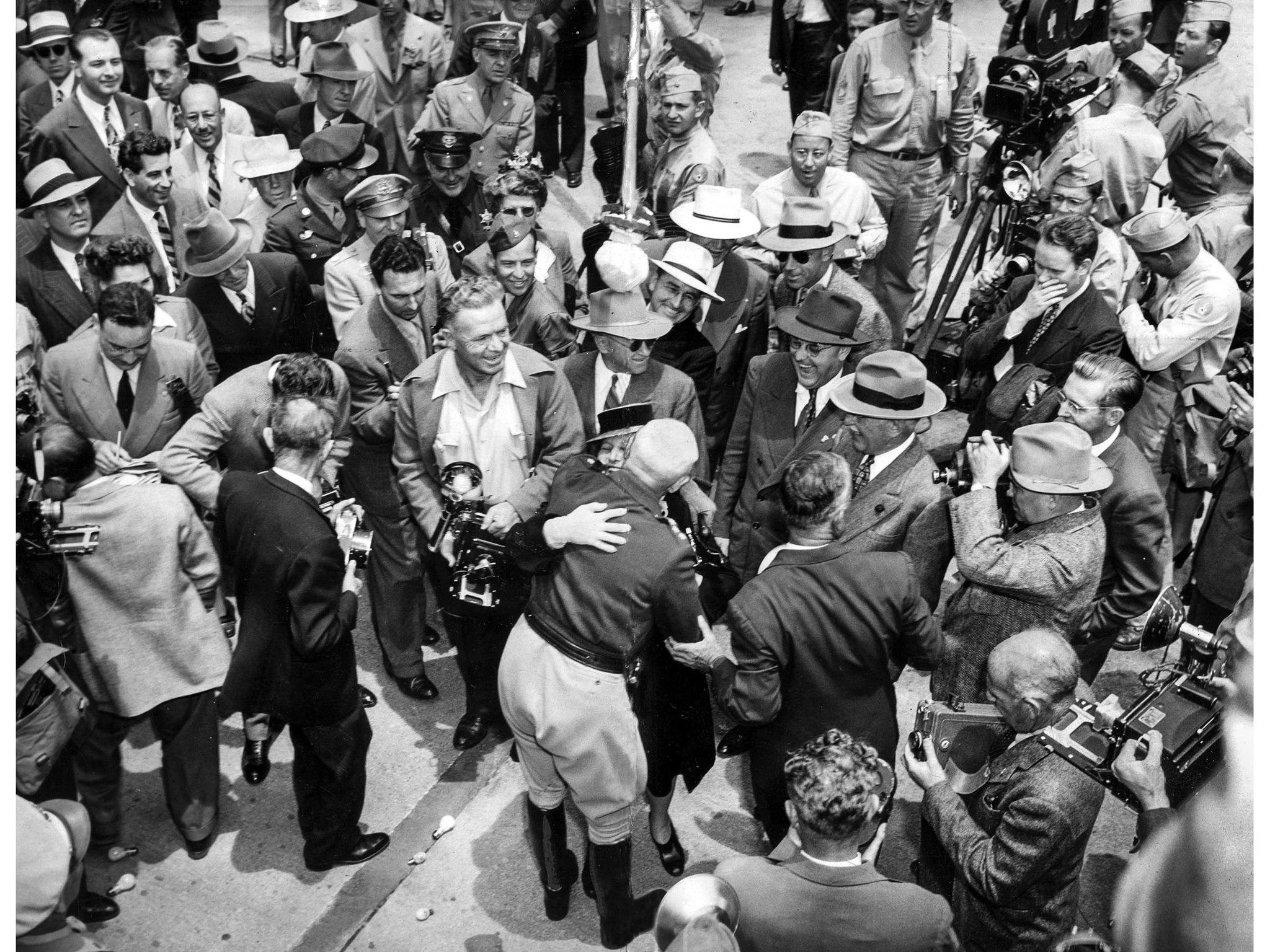 June 9, 1945: Photographers swarm Gen. George S. Patton Jr., as he embraces Mrs. Frances P. Graves,