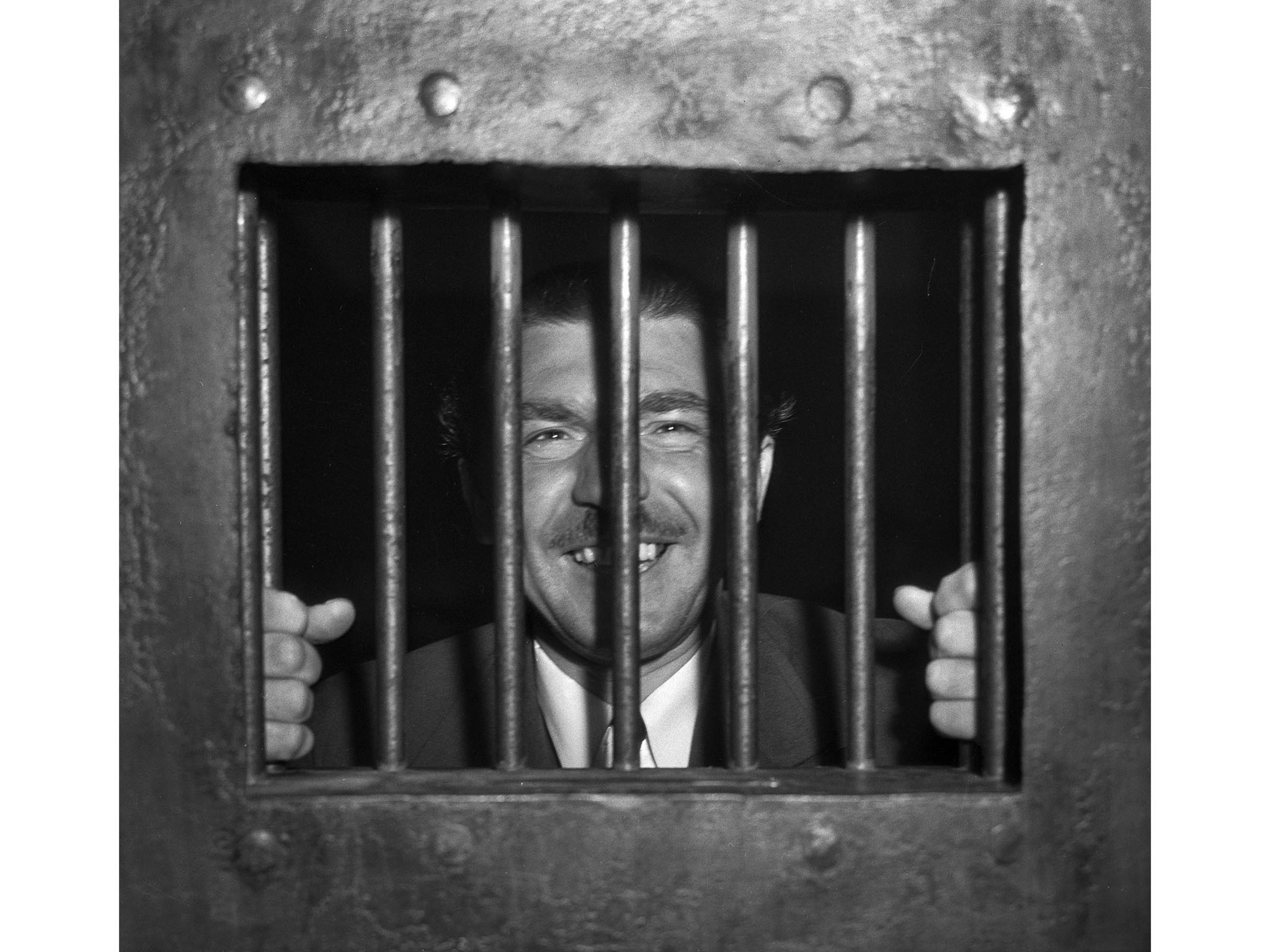 April 10, 1936: Andrew Schwarzman, writer, is shown behind bars after disturbing the peace. He was s