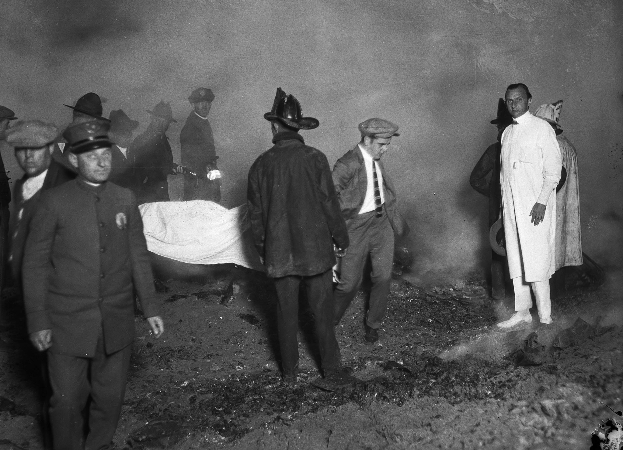 May 31, 1924: Rescue workers carry the covered remains of a victim of the fire at the Hope Developme