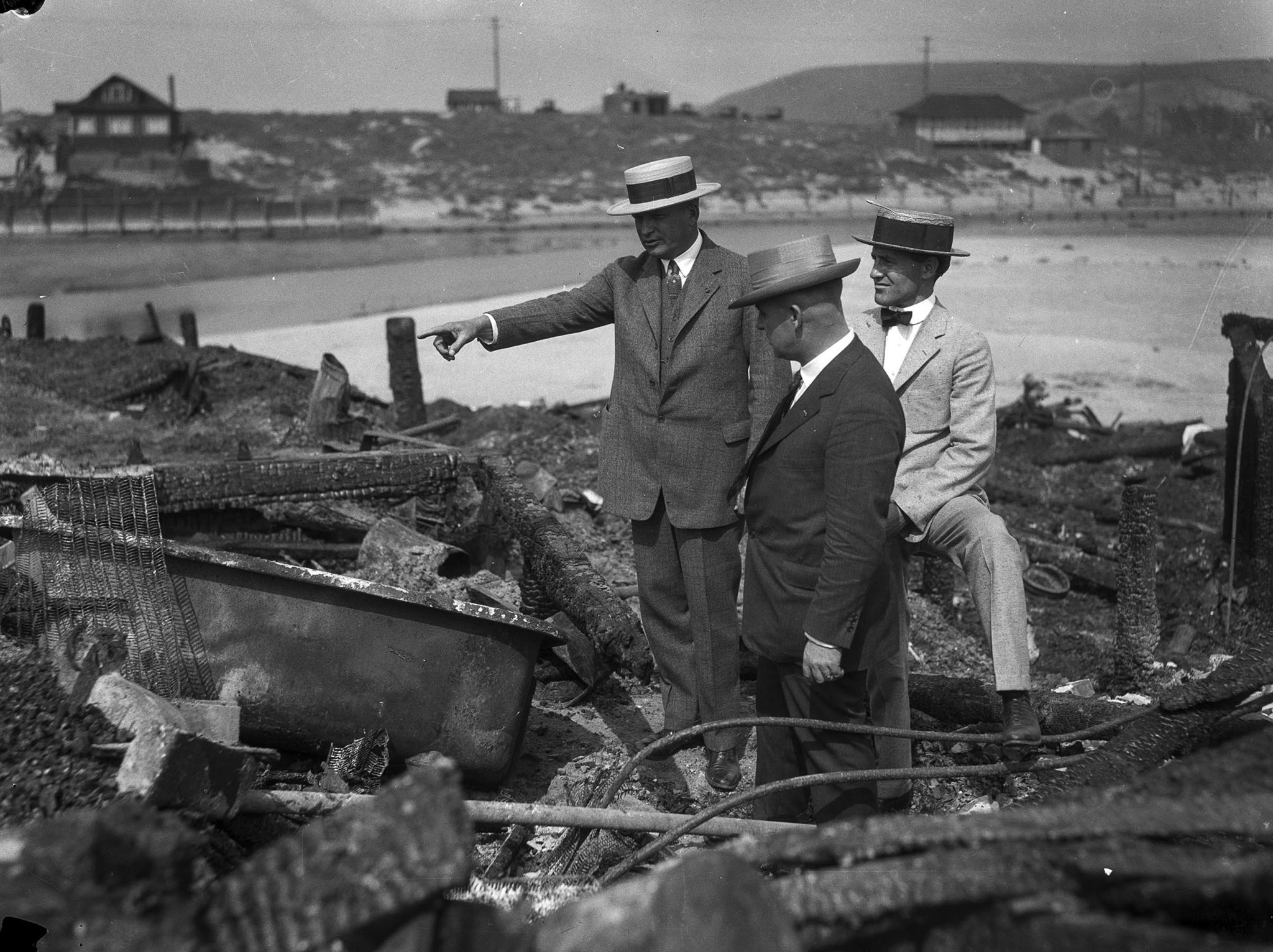 June 1924: Three men look over the charred remains of the Hope Development School for mentally disa