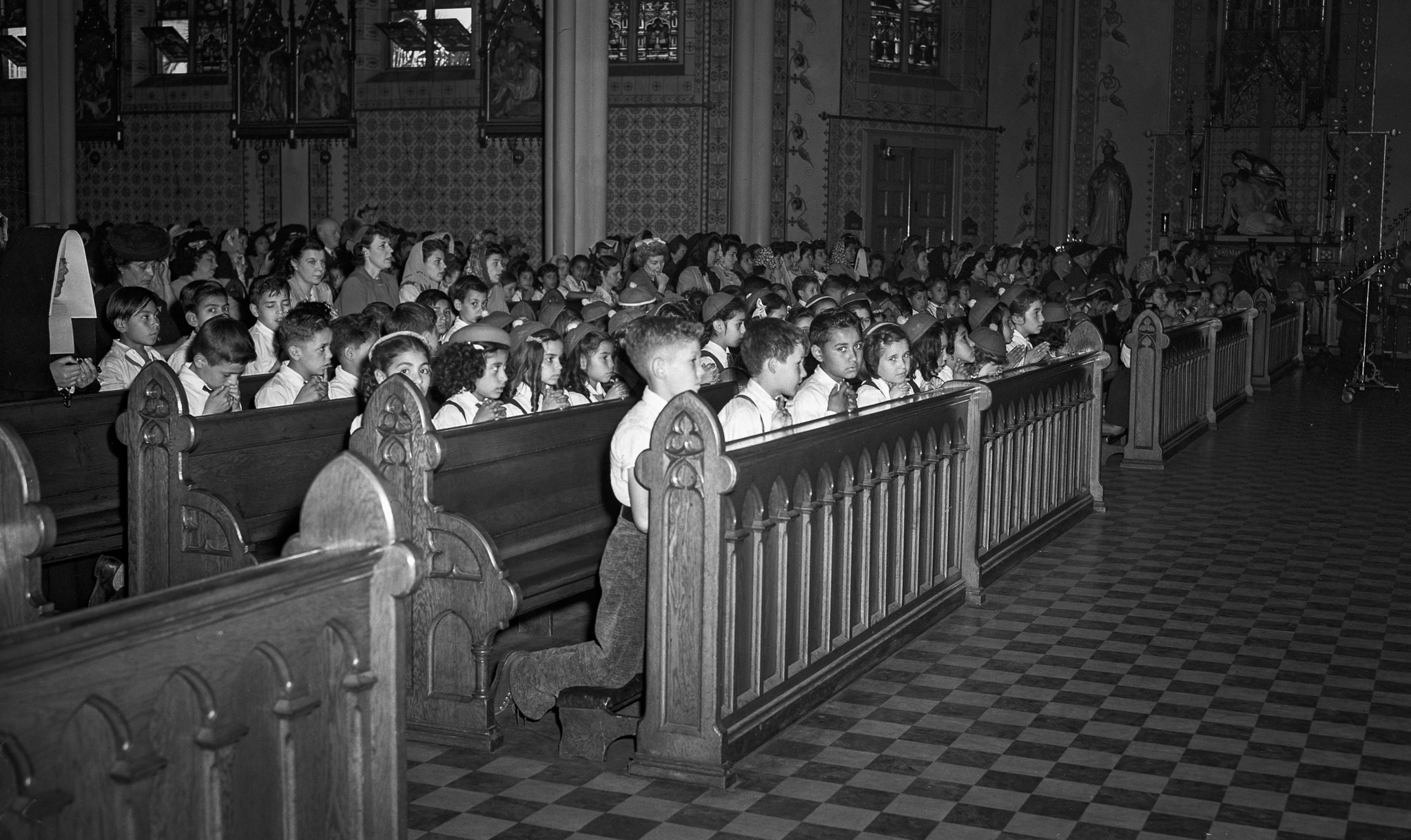 June 6, 1944: Children in prayer at noon on D-Day at St. Josephs Church located at 12th and Los Ange