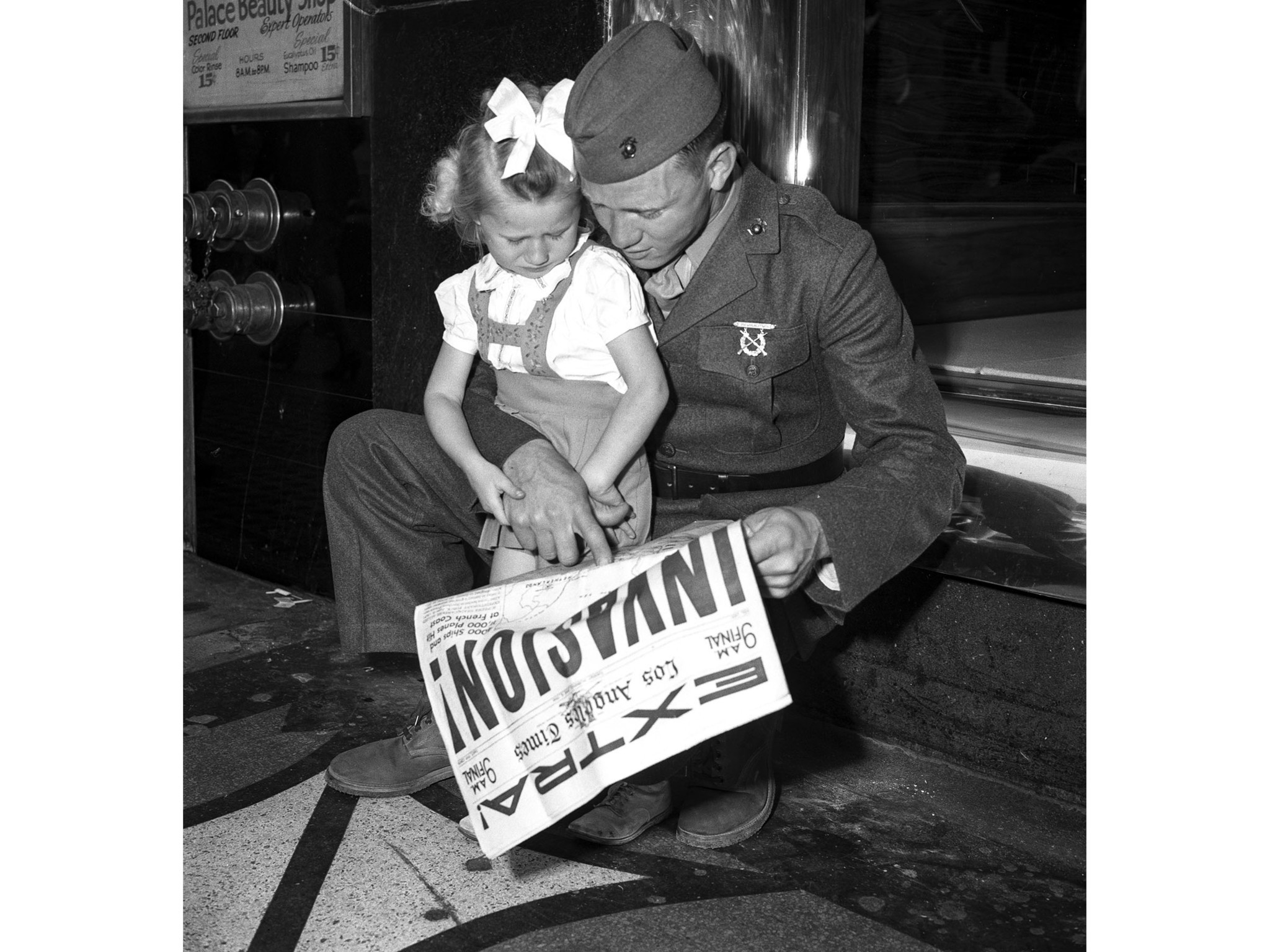 June 6, 1944: Marine Pvt. Calvin H. Laxson points out the invasion map to his daughter Cathryn, 3. T