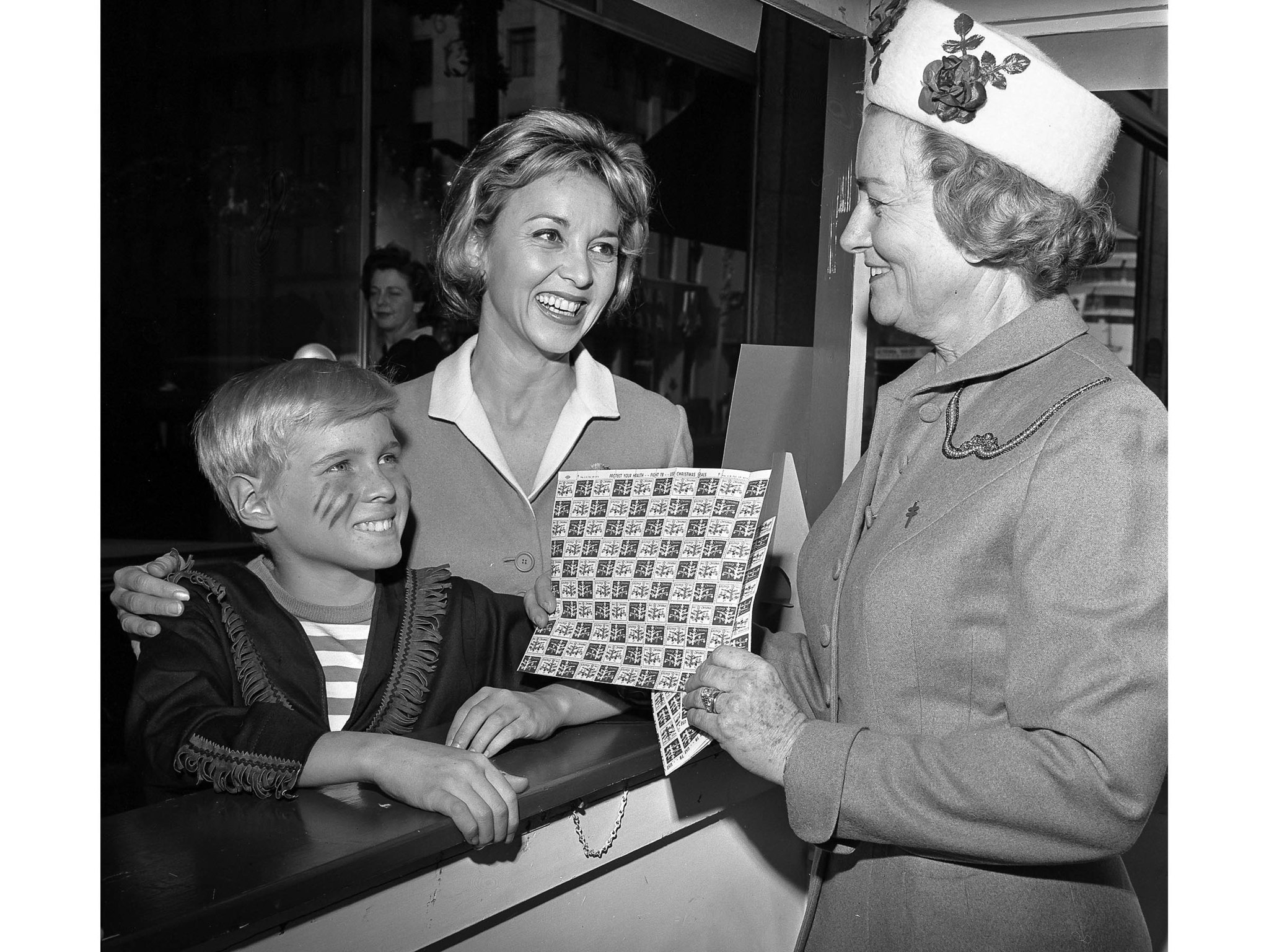 November 1962: Jay North left, still wears Dennis the Menace makeup as he helps actress Beverly Garl