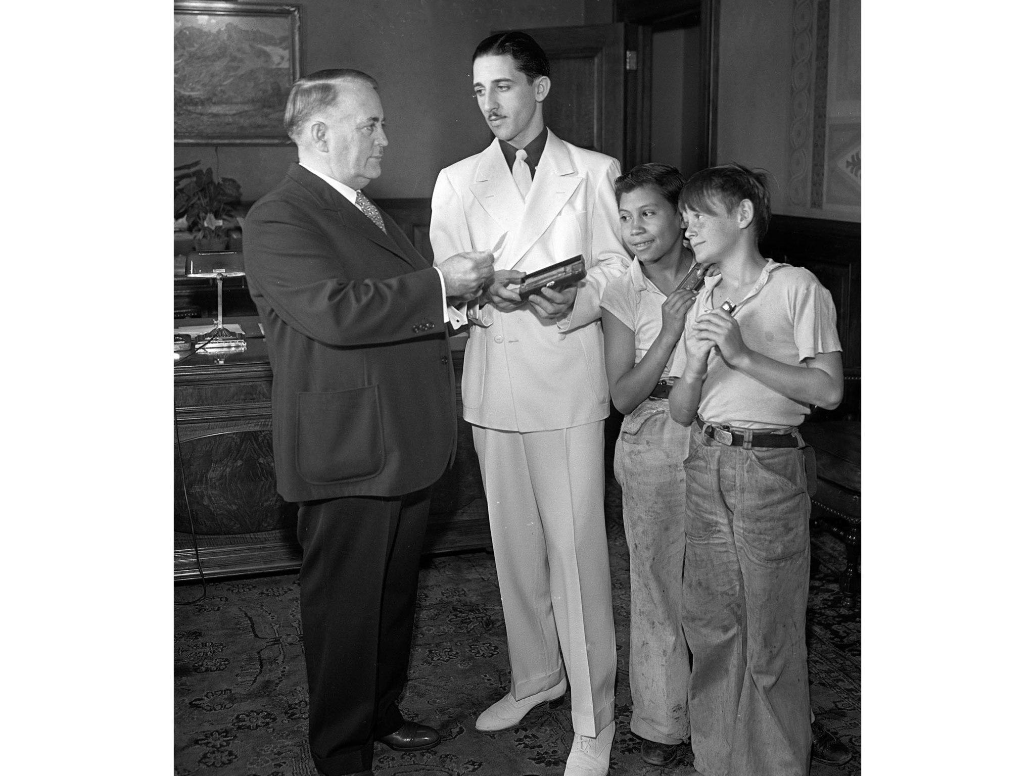 June 27, 1935: From left, Mayor Frank Shaw, Harmonica teacher Kenneth Milton, Manuel Martinez, and H