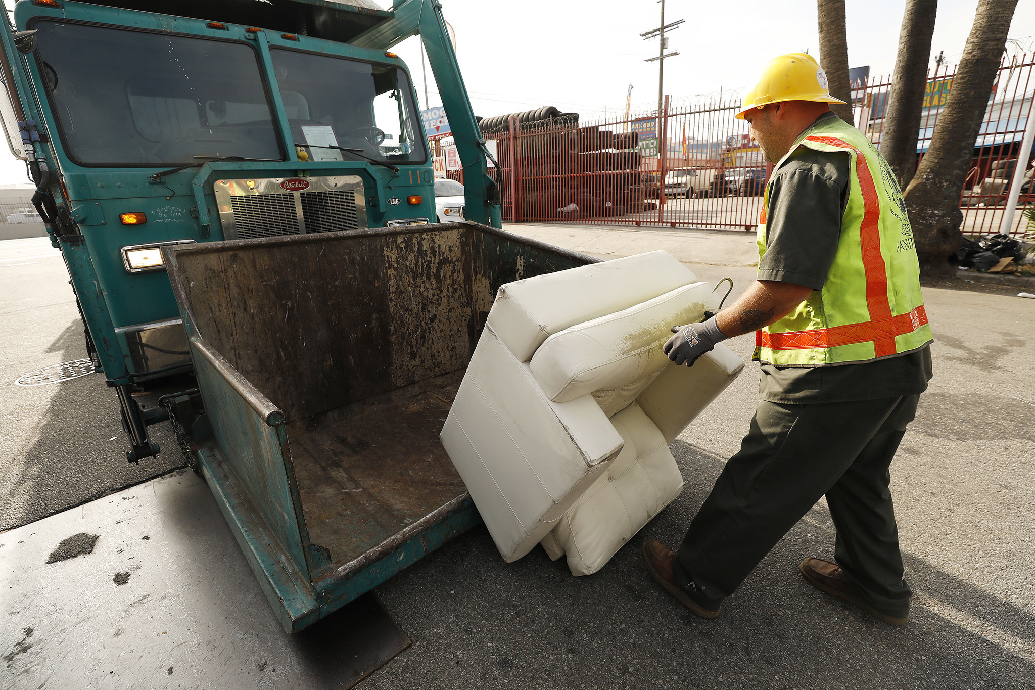 A discarded sofa is removed