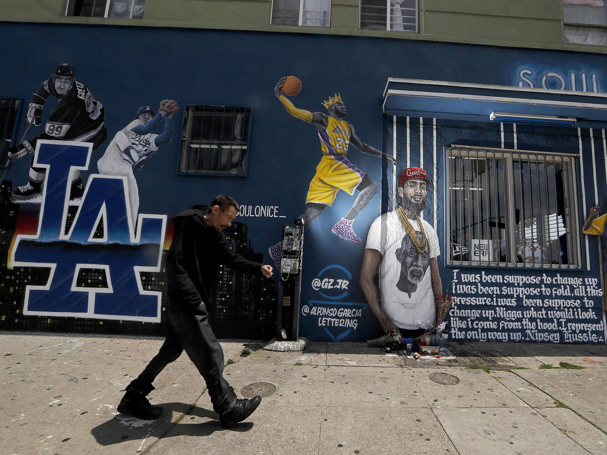 Flowers sit at Nipsey Hussle mural