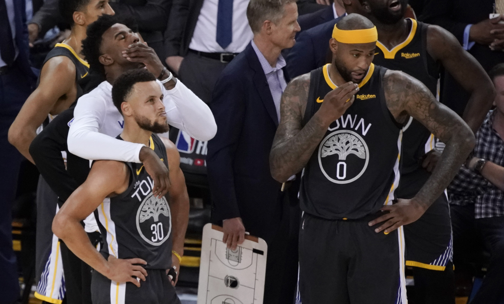 Golden State Warriors guard Stephen Curry, bottom left, reacts with forward Jordan Bell, top left, a