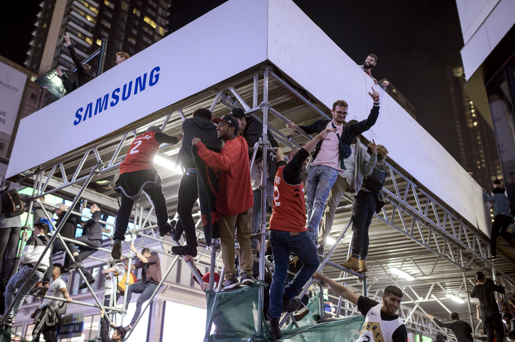 Toronto Raptors supporters climb a scaffold as fans celebrate in the streets after the Raptors defea