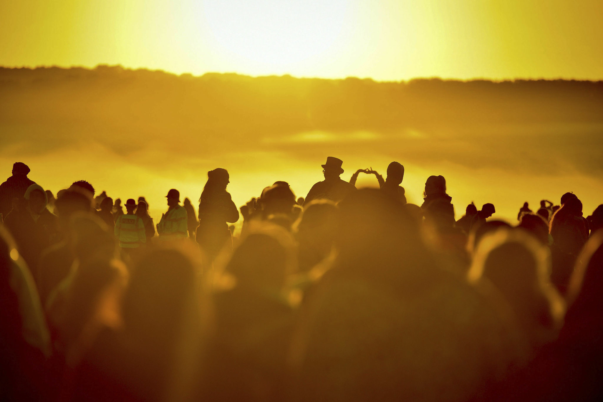 People turn to face the rising sun at Stonehenge as crowds of people gather to celebrate the dawn of